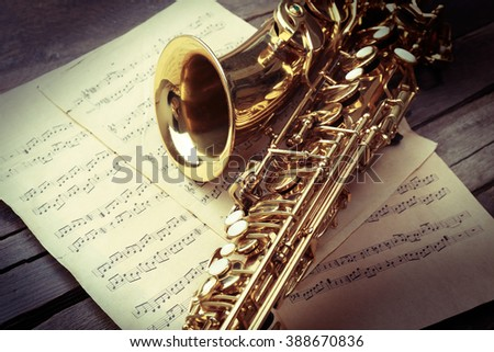 Golden saxophone with musical notes on wooden background, close up - stock photo