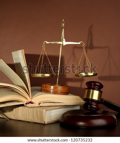 Golden scales of justice, gavel and books on brown background