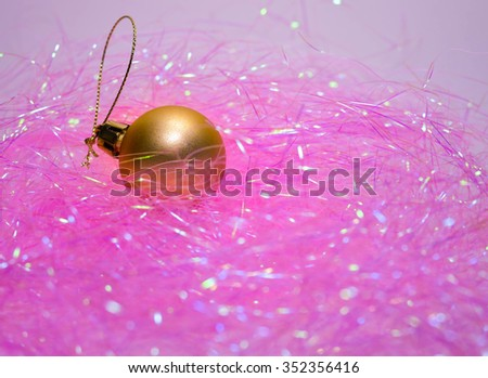 golden shiny christmas ball on a pale pink background  - stock photo