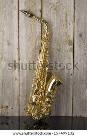 golden shiny saxophone on wood background - stock photo