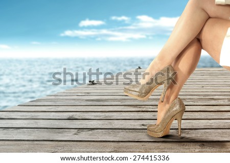 golden shoes and woman legs and sea and sky of blue