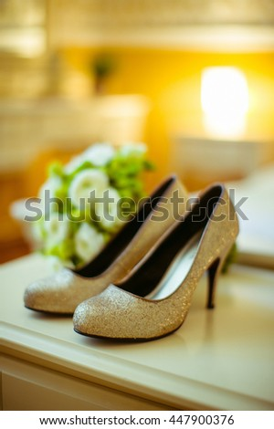 Golden shoes stand behind a wedding bouquet on the wardrobe - stock photo