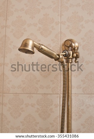 Golden shower head on wall with faience. Vintage shower head - stock photo