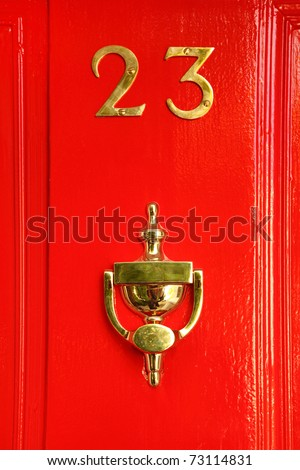 golden sign on red wooden door; 23 and cup; reflection in cup - stock photo