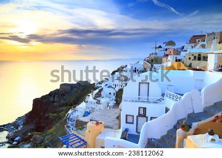 Golden sky and sea near white buildings of Oia village at sunset, Santorini island, Greece - stock photo