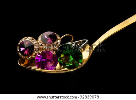Golden spoon with jewelry such as rings with stones and rings - stock photo