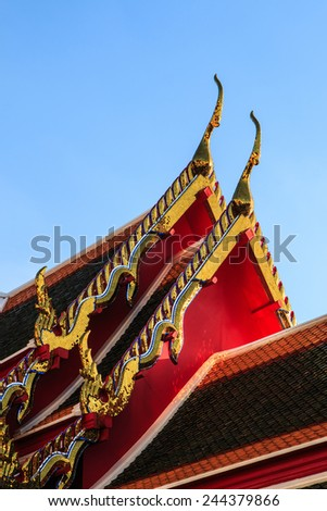 Golden stain-glass ornament on wat thai roof in sunshine - stock photo