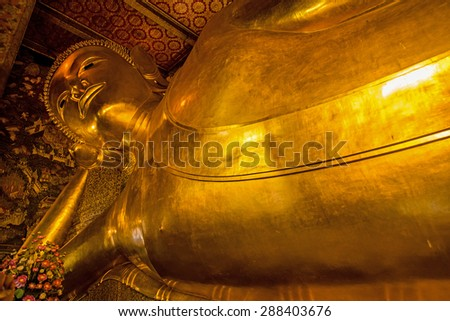 Golden statue of the large reclining Buddha at Wat Pho temple in Bangkok, Thailand. - stock photo