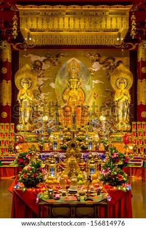 Golden statues and art inside a Buddhist Temple in Singapore - stock photo