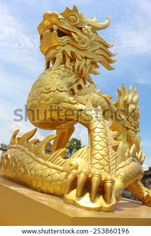 Golden stone dragon statue in Vietnam, Hue - stock photo