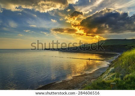 Golden sunlight illuminates the sea, rocks and cliffs on the Jurassic Coastline of South Dorset - stock photo