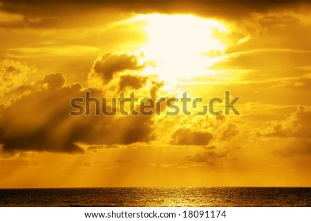 Golden sunlight through clouds on the sea - stock photo