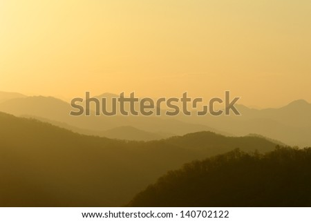Golden sunrise above layers of misty mountains.