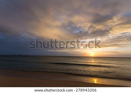 Golden sunrise on desert beach and scenic cloudscape during monsoon time. Tourist resort in Nilaveli, Trincomalee region, Sri Lanka, upgrowing travel destination after end of the war. Blurred motion.  - stock photo