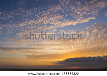 Golden sunrise with cloudy sky. - stock photo