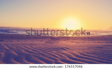 Golden sunset above the ocean and beach, retro vintage look - stock photo