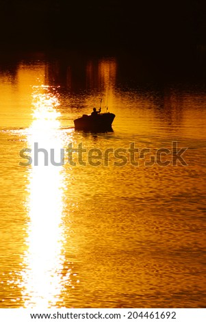 Golden Sunset on the lake, fishing boat, Quebec, Canada - stock photo