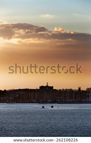 Golden sunset over Corio Bay Geelong Australia. Silhouettes of industrial buildings on the horizon. - stock photo