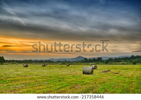 Golden sunset over farm field with hay bales - stock photo