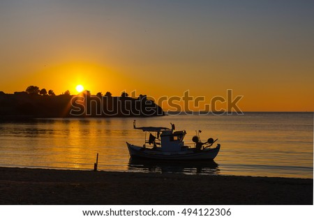 Golden sunset over sea in Greece coast and boat ship silhouette