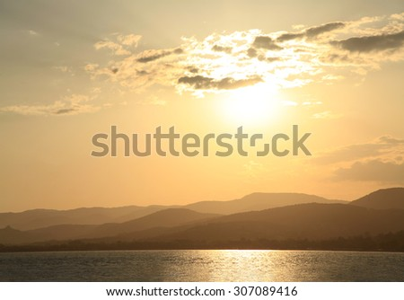 Golden Sunset Over the Mountainous Shoreline - stock photo