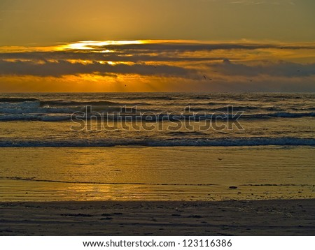 Golden Sunset Over the Ocean with Waves in the Foreground - stock photo