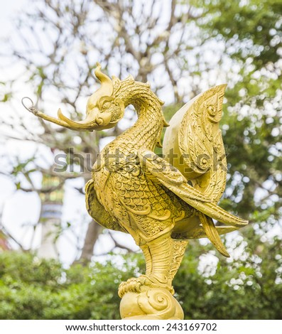 golden swan statue on nature background