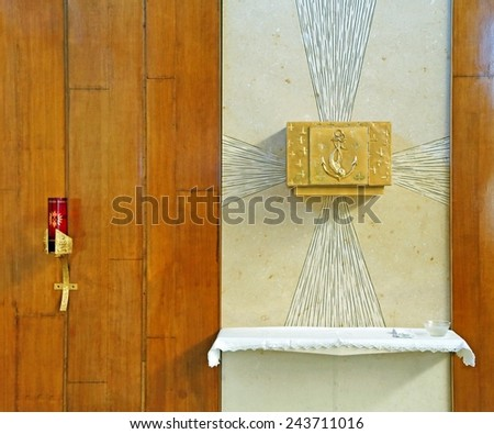 Golden Tabernacle with consecrated hosts in the Christian Church with a candle - stock photo