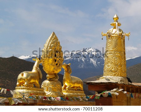 Golden Tibetan deer statues with mountain background, Zongdian, Yunnan, Tibet - stock photo