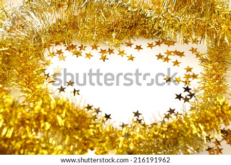 Golden tinsel garland frame and star confetti - stock photo