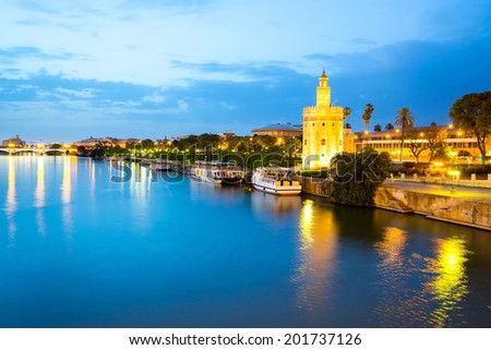 Golden Tower with cityscape and river of Sevilla at night Seville, Spain - stock photo