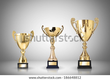 golden trophies on gray background - stock photo