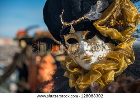 Golden Venetian Carnival Mask Wonderful mask participant of the carnival celebrations in St. Mark's basin. Blurred background. - stock photo