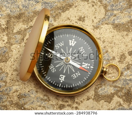 Golden vintage compass opened on soil background - stock photo