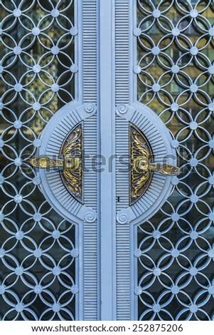 Golden vintage door handles on glass and metal decorative doors in Bulgarian castle - stock photo