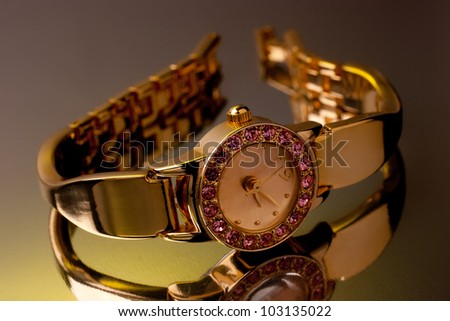 Golden watch decorated with gems with reflection - stock photo