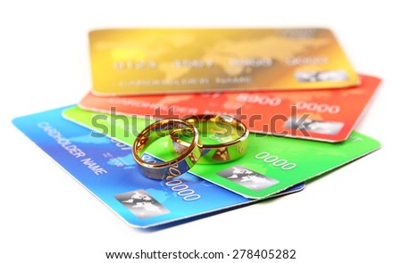 Golden wedding rings and credit cards, isolated on white. Marriage of convenience concept - stock photo
