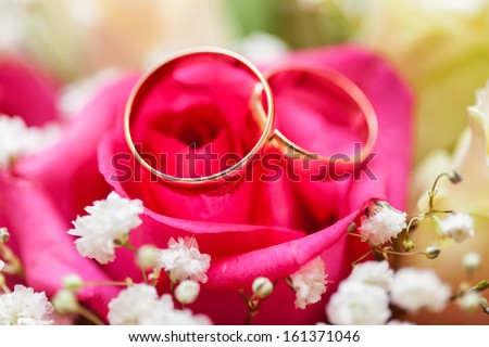Golden wedding rings on bridal bouquet. Close-up - stock photo