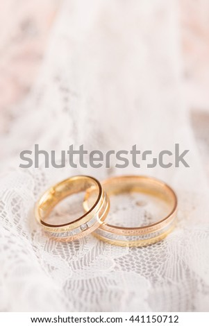 Golden wedding rings on pastel lace. Shallow focus