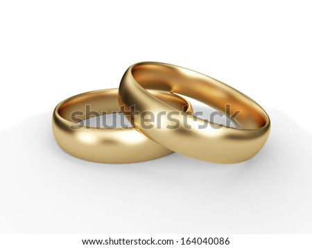 Golden wedding rings on white background - stock photo