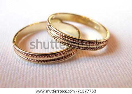 Golden wedding rings on white matter - stock photo
