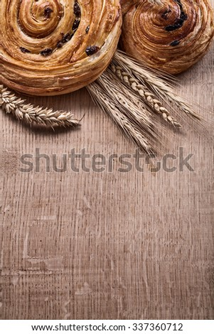 Golden wheat ears raisin baked buns on oaken wooden board food and drink concept. - stock photo