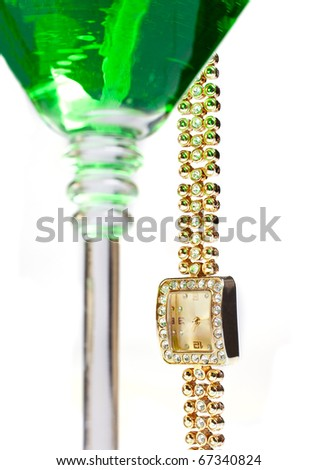 Golden wrist watch hanging from martini glass - stock photo