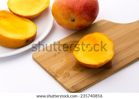 Golden yellow third of a trisected mango. Its ripe fruit flesh bedewing the wooden cutting board beneath. The remaining two thirds on a white plate next to an entire mango. White background. - stock photo