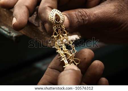 Goldsmith holding an unfinished 22 carat gold earring in his hard working hands and fine gold dust on the hands. Shallow DOF - focus on the earring top - stock photo