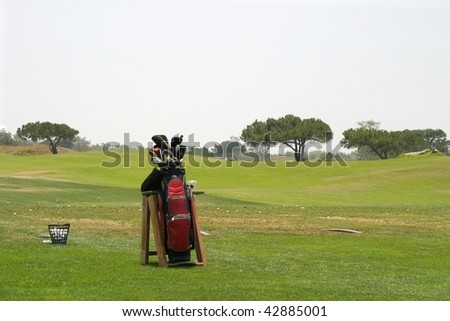 Golf Bag with a basket of golfballs and a driving range in the background. - stock photo