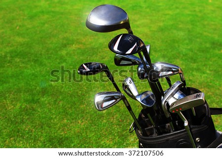 Golf bag with clubs on green field, close up - stock photo