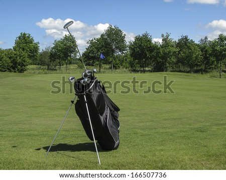 Golf bag with irons and putter sticking out near golf green - stock photo
