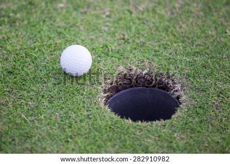 Golf ball about to enter the hole - stock photo