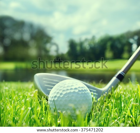 Golf ball and club on golf course - stock photo